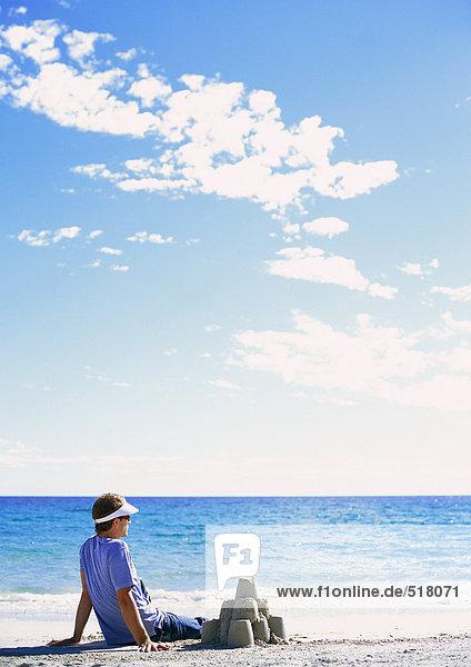 Mann in der Nähe der Sandburg mit Blick aufs Meer