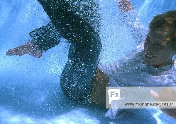 Voll bekleideter Mann am Boden des Swimmingpools  lächelnd