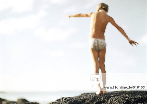 Kinderbalancieren auf Fels  Rückansicht  unscharf