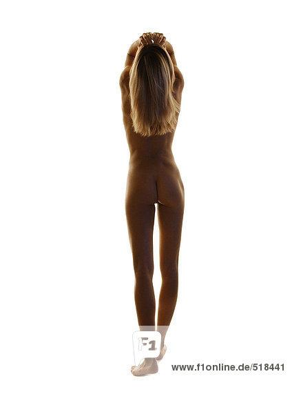 Nackte Frau stehend mit Händen auf dem Kopf  volle Länge  Rückansicht