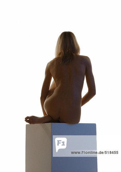 Nackte Frau auf Sockel sitzend  Rückansicht