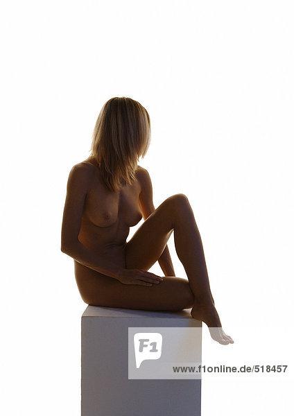 Nackte Frau sitzend mit Knie oben auf Sockel