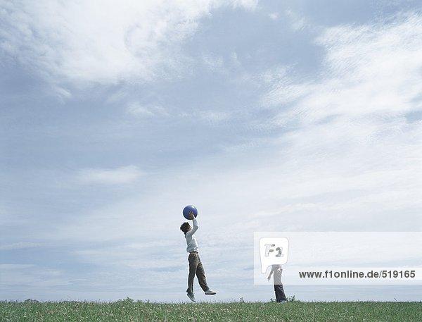 Junger Mann und Frau auf Rasen in der Ferne spielen mit Ball  Mann springt zum Ball fangen