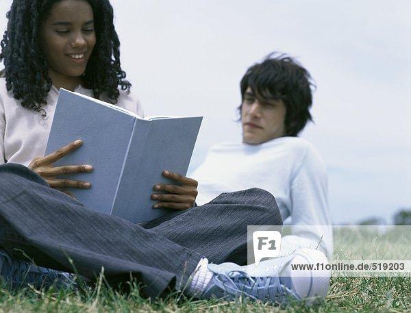 Junge Frau sitzt auf Gras und liest Buch  junger Mann lehnt sich auf den Ellbogen hinter ihr.