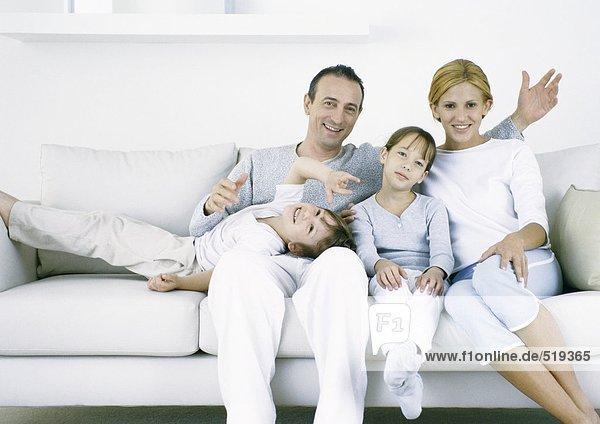 Eltern  die mit Tochter und Sohn auf dem Sofa sitzen und in die Kamera schauen.