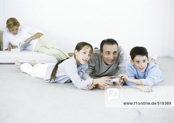Mann und Junge und Mädchen liegen auf dem Boden und spielen Videospiel  Frau liest im Hintergrund