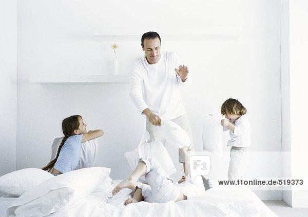 Mädchen und Jungen bei Kissenschlacht mit Mann