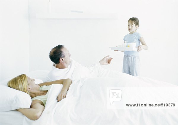 Mädchen bringt Eltern Frühstück ins Bett