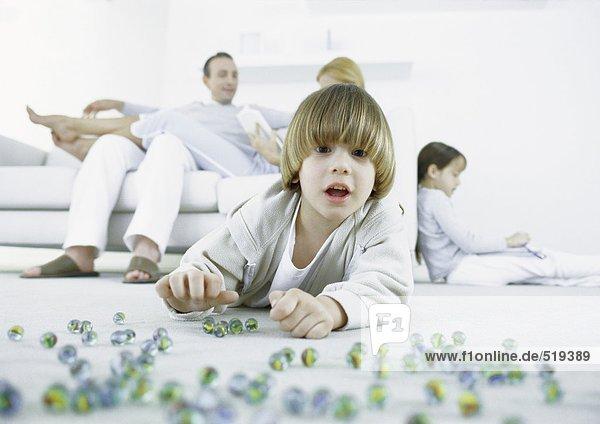 Junge liegt auf dem Boden und spielt Murmeln  Eltern und Schwester sitzen im Hintergrund.