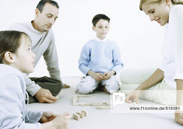 Mädchen und Junge mit Eltern beim Domino spielen auf dem Boden