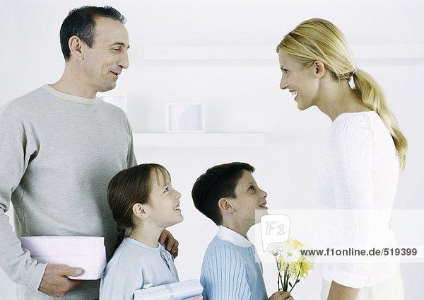 Mann mit Junge und Mädchen vor Frau mit Geschenken und Blumen