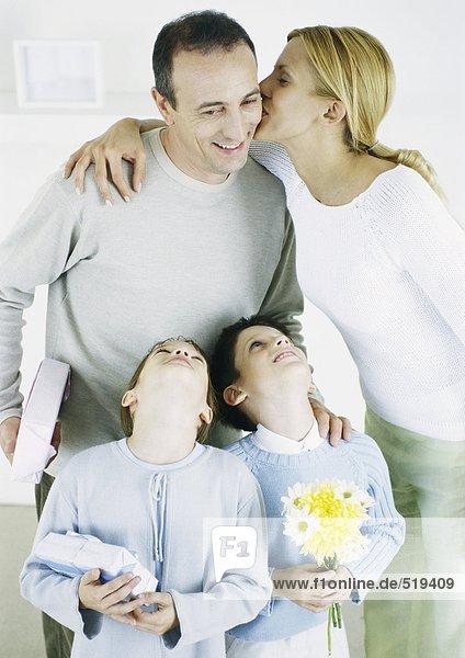 Frau küsst Mann auf Wange  Mädchen und Junge schauen mit Köpfen nach oben