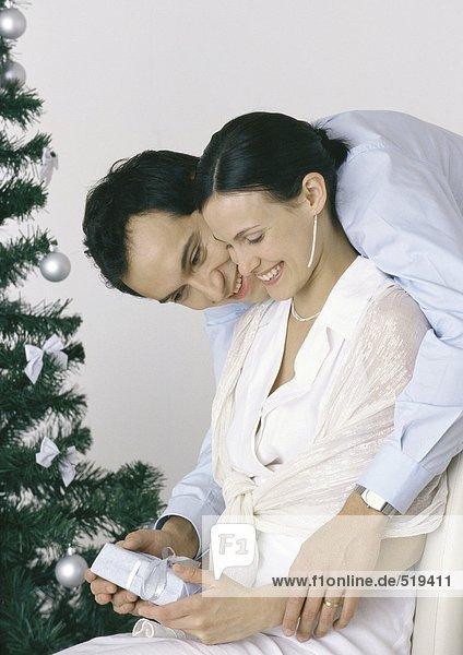 Frau hält Geschenk  Mann beugt sich über die Schulter  Weihnachtsbaum im Hintergrund