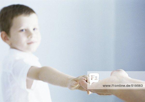 Junge  der die Hand eines Erwachsenen berührt.