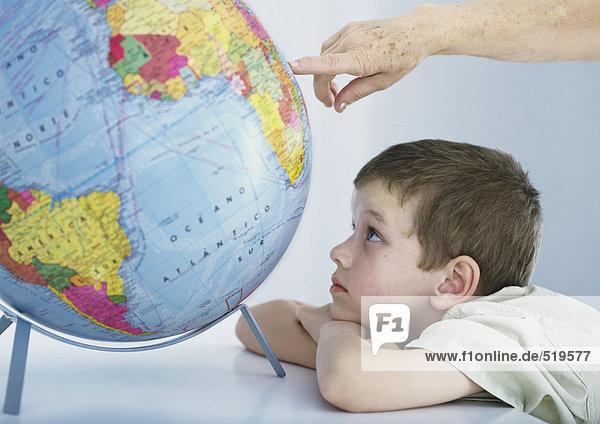 Junge schaut auf den Globus  die Hand einer älteren Person zeigt auf den Globus.