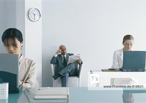 Zwei Frauen arbeiten an Laptops im Büro  Geschäftsmann sitzt im Stuhl und liest Zeitung im Hintergrund.