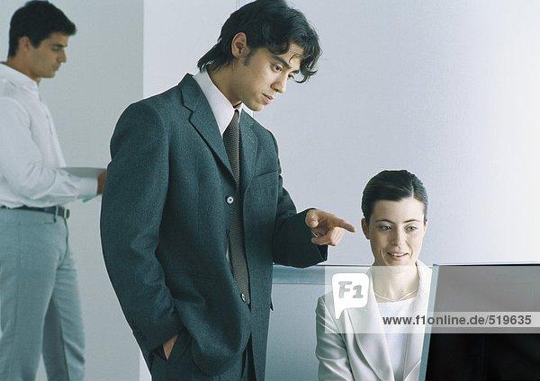 Zwei Kollegen  die auf den Computer schauen.