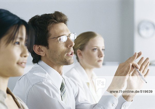Business people in meeting  man with glasses gesturing