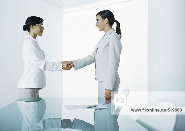 Zwei junge Frauen in Anzügen mit Händeschütteln