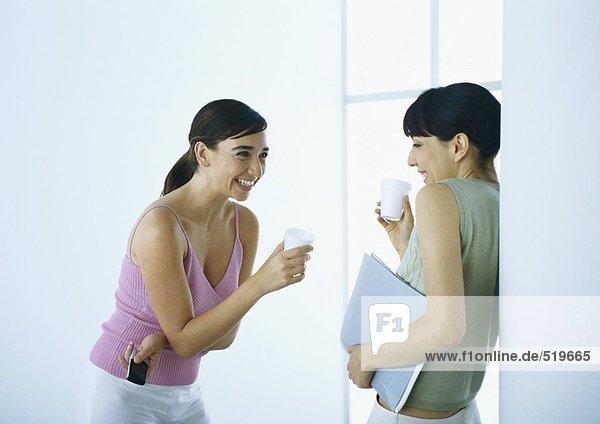 Zwei Frauen  die mit Tassen stehen und lachen.