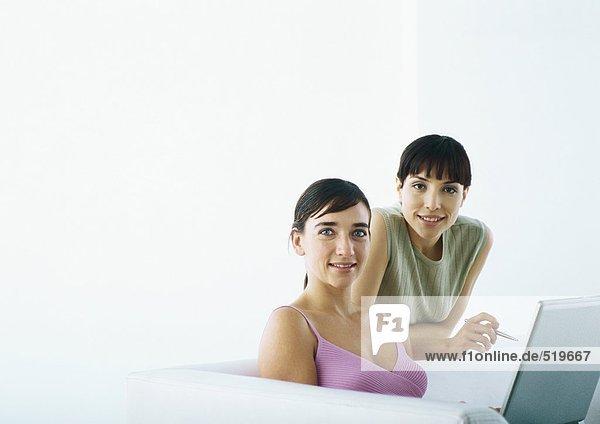 Frau sitzend auf Sofa mit Laptop  zweite Frau hinter dem Sofa lehnend
