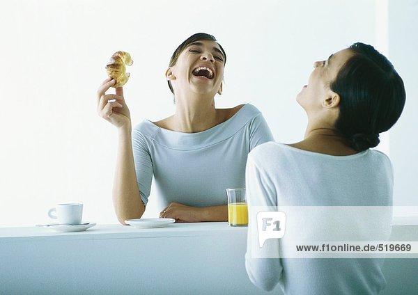Zwei Frauen auf beiden Seiten der Bar beim Frühstücken  lachend