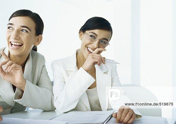 Zwei Geschäftsfrauen lachend  zur Seite schauend