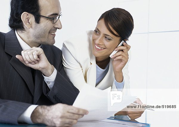 Businesswoman talking on cell phone smiling at businessman next to her