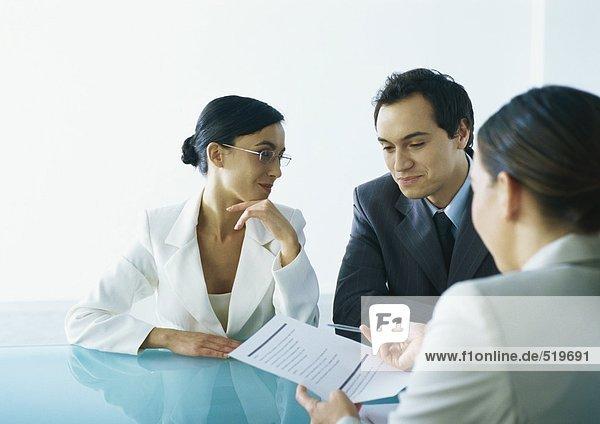 Geschäftsmann und Geschäftsfrau sitzen am Tisch gegenüber der Geschäftsfrau  die das Dokument und den Stift hält.