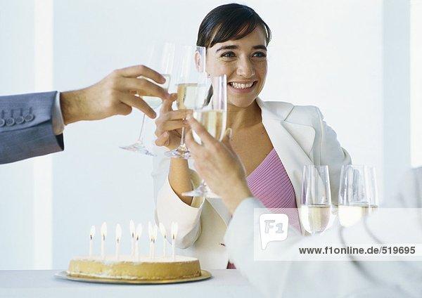 Geschäftsleute klirren bei Geburtstagskuchen mit Champagner.