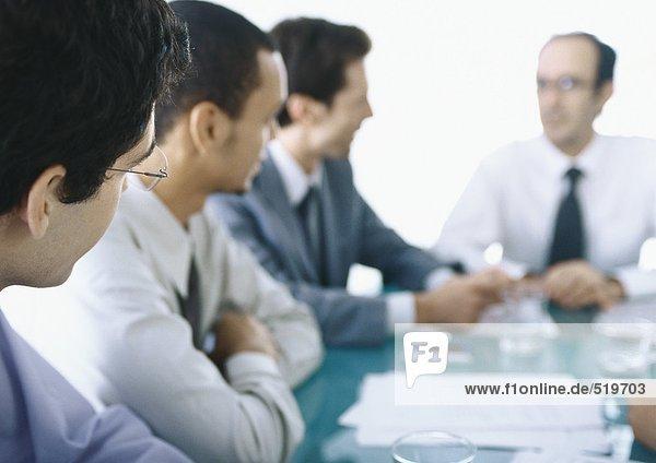 Geschäftsleute  die am Tisch sitzen und sich treffen