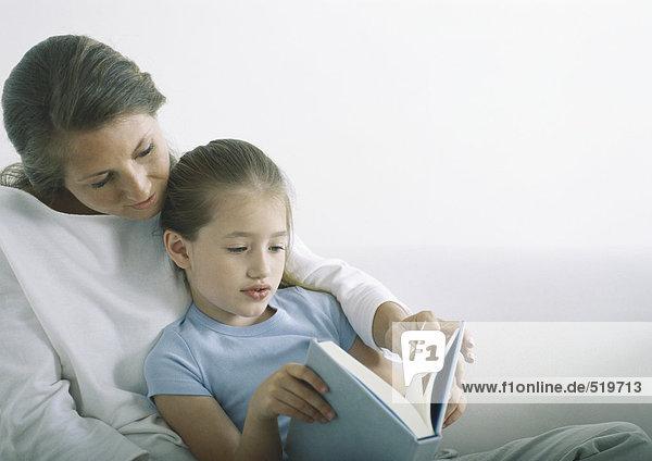 Frau und Mädchen lesen gemeinsam Buch