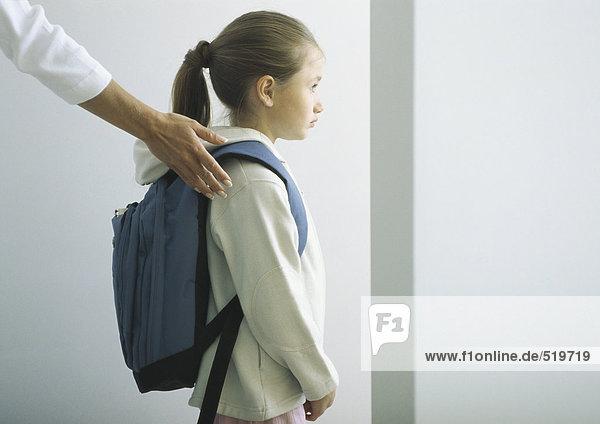 Frauenhand auf Schulter des Mädchens mit Rucksack