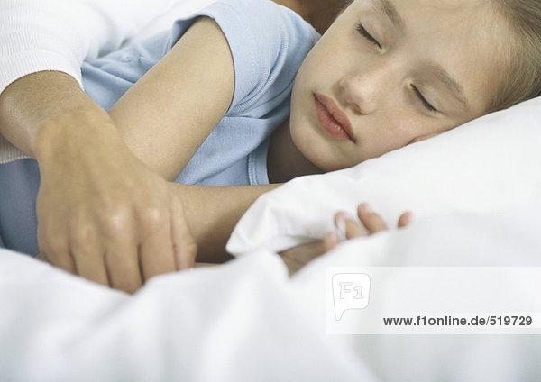 Mädchen schläft mit dem Arm der Frau über ihr