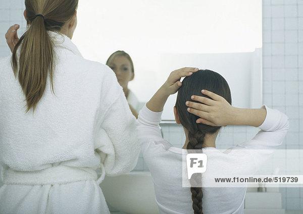 Frau und Mädchen beim Frisieren der Haare  Rückansicht