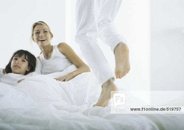 Junge springt auf Bett  Frau und Mädchen im Bett im Hintergrund