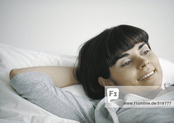 Frau mit der Hand hinter dem Kopf liegend
