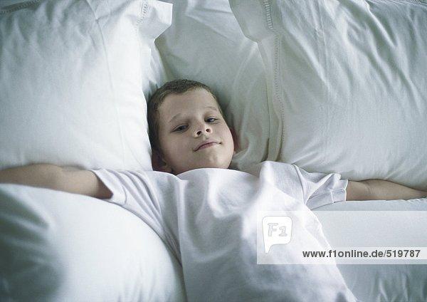 Junge auf dem Bett liegend mit ausgestreckten Armen