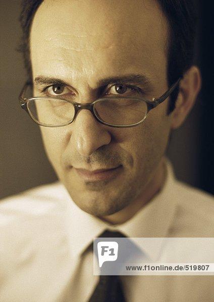 Mann schaut über den Brillenrand  Portrait