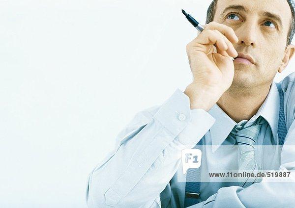 Mann hält Stift in der Nähe des Gesichtes  schaut nach oben.