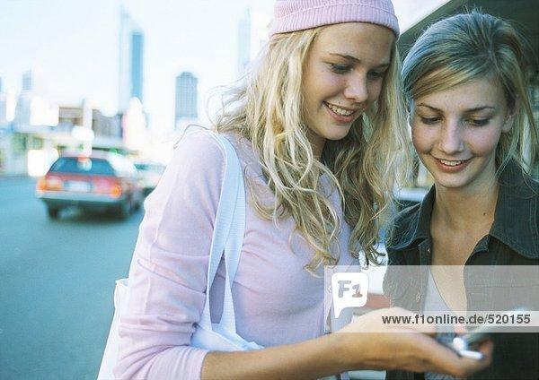 Zwei Teenager-Mädchen  die in der Nähe der Straße stehen und auf das Handy schauen.