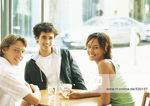 Group of young people sitting at table in café  smiling at camera