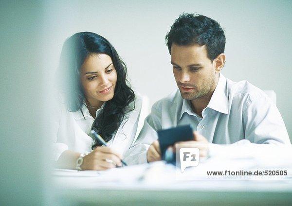 Junge Erwachsene bei der Prüfung von Dokumenten  bei der Berechnung von
