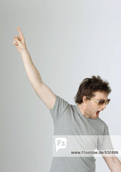 Junger Mann mit erhobener Hand in der Luft und offenem Mund  mit Sonnenbrille  Portrait