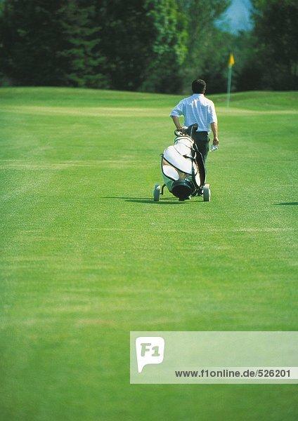 Golfer zieht Golftasche auf Grün