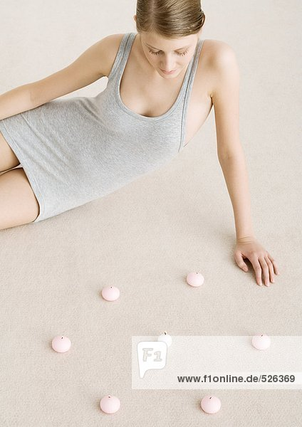 Frau auf dem Boden sitzend mit Kerzenkreis  Hochwinkelansicht