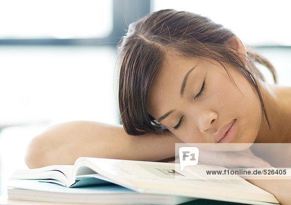 Junge Frau ruht Kopf auf Büchern  mit geschlossenen Augen