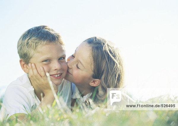 Junge und Mädchen liegen auf Gras  Mädchen küsst Junge auf Wange