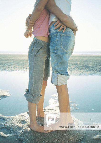 Zwei Kinder stehen am Strand und umarmen sich.
