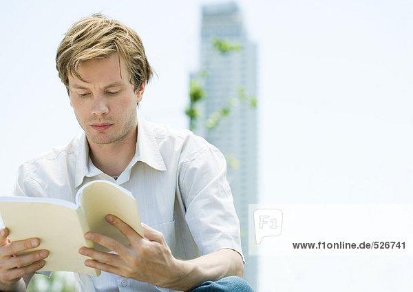 Junger Mann liest Buch  Wolkenkratzer im Hintergrund